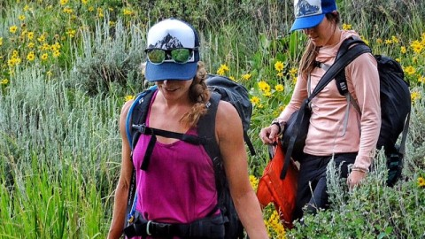#Adventuregirls @fifty.shades.of.purple and @sjstasi frolic through the wildflowers il after climbing Rodeo wall in #jacksonhole. #avalon7 #adventuremore  Get your own Majestic Trucker hat at www.avalon7.co